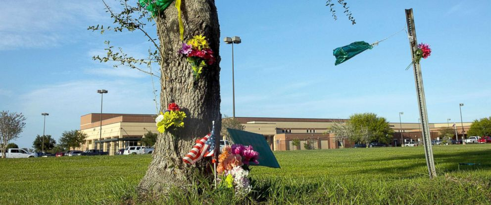 PHOTO: Flags and flowers sit around a tree outside the Santa Fe High School as the town comes to gather for a vigil before the first day of school, Aug. 19, 2018, in Santa Fe, Texas.