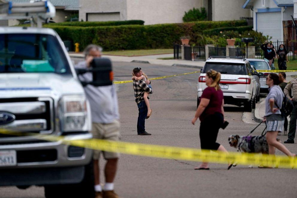 PHOTO: Neighbors watch fire crews near the scene of a small plane crash, Oct. 11, 2021, in Santee, Calif.