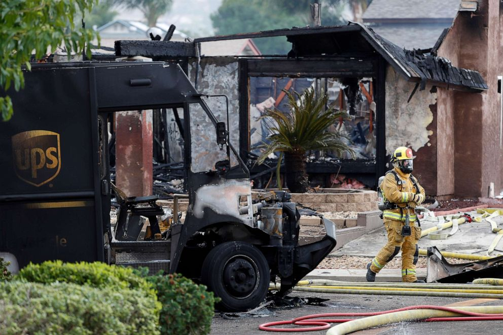 PHOTO: A firefighter walks by the debris of a fatal plane crash on Oct. 11, 2021, in Santee, Calif. A small plane crashed into a UPS truck and then struck two homes, which were destroyed by fire.