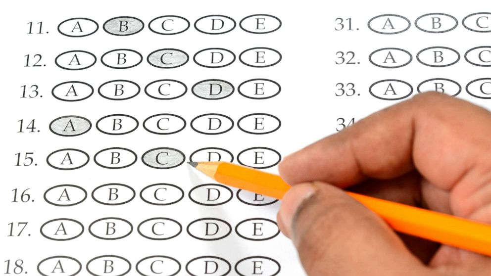 A student appears to be filling out a multiple choice exam paper with a pencil.