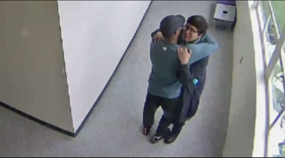 PHOTO: A still from security video shows Parkrose High School coach Keanon Lowe hugging a student who brought a shotgun to school.