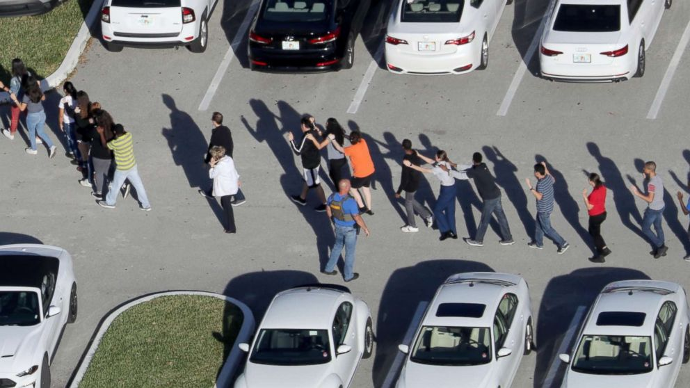 Students are evacuated by police from Marjory Stoneman Douglas High School in Parkland, Fla., after a mass shooting on Feb. 14, 2018.
