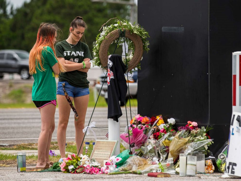 PHOTO: Kalysta Dodson, left, and Reagyn Murphy, sophomores at Santa Fe High School, look at a memorial for the victims of the Santa Fe High School shooting in Santa Fe, Texas.