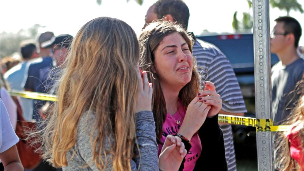Students released from a lockdown are overcome with emotion following following a shooting at Marjory Stoneman Douglas High School in Parkland, Fla., Feb. 14, 2018.