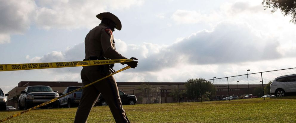 A Texas Department of Public Safety officer places crime scene tape across Santa Fe High School the day after a shooting that left 10 dead.