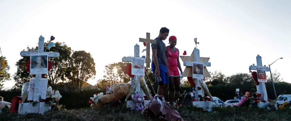 PHOTO: Denyse Christian, visits a makeshift memorial with her son Adin Christian, 16, a student at the school, outside the Marjory Stoneman Douglas High School.