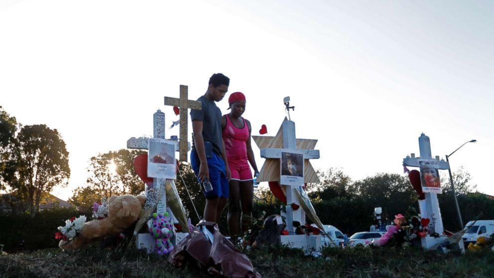 Denyse Christian, visits a makeshift memorial with her son Adin Christian, 16, a student at the school, outside the Marjory Stoneman Douglas High School.