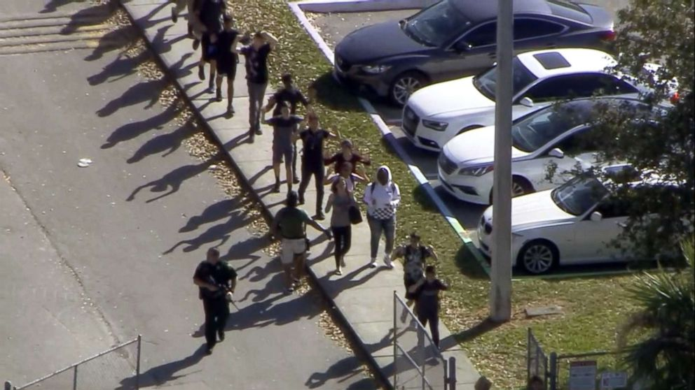 Students walk with an armed escort after reports of a shooting at Stoneman Douglas High School in Parkland, Fla., Feb. 14, 2018.