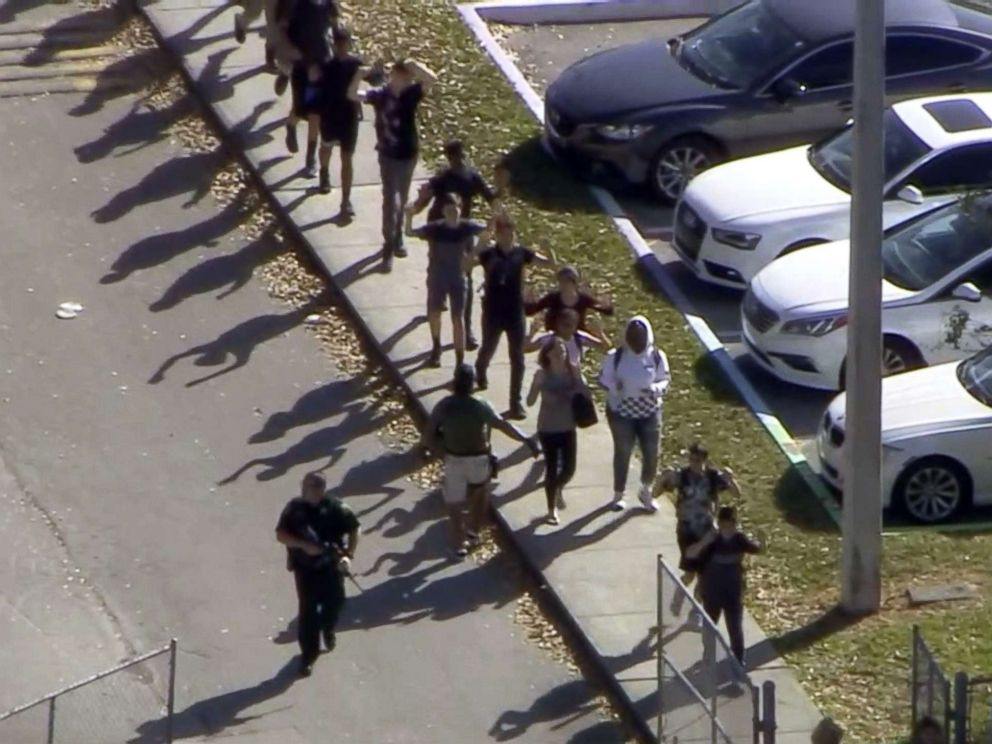 PHOTO: Students walk with an armed escort after after reports of a shooting at Stoneman Douglas High School in Parkland, Fla., Feb. 14, 2018.