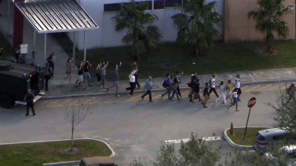 People emerge from a building with their hands raised after reports of a shooting at Stoneman Douglas High School in Parkland, Fla., Feb. 14, 2018.
