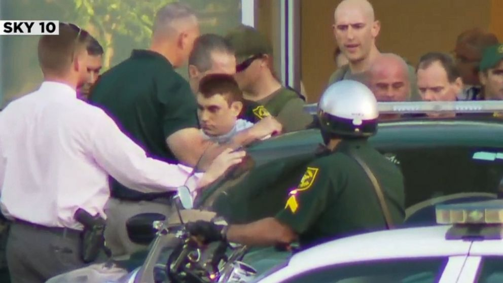 Nikolas Cruz, the suspect in a shooting at Marjory Stoneman Douglas High School in Parkland, Fla., is escorted out of a hospital and into a police car.