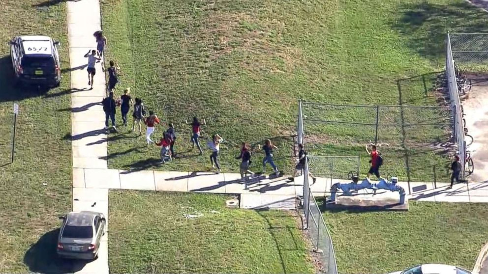 Students are evacuated from Marjory Stoneman Douglas High School after a shooting in Parkland, Fla., Feb. 14, 2018.