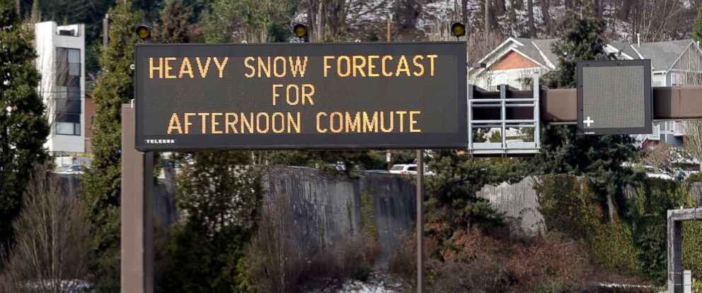 PHOTO: Light traffic passes by as a highway sign over Interstate 90 warns of expected snow later in the day Friday, Feb. 8, 2019, in Seattle.