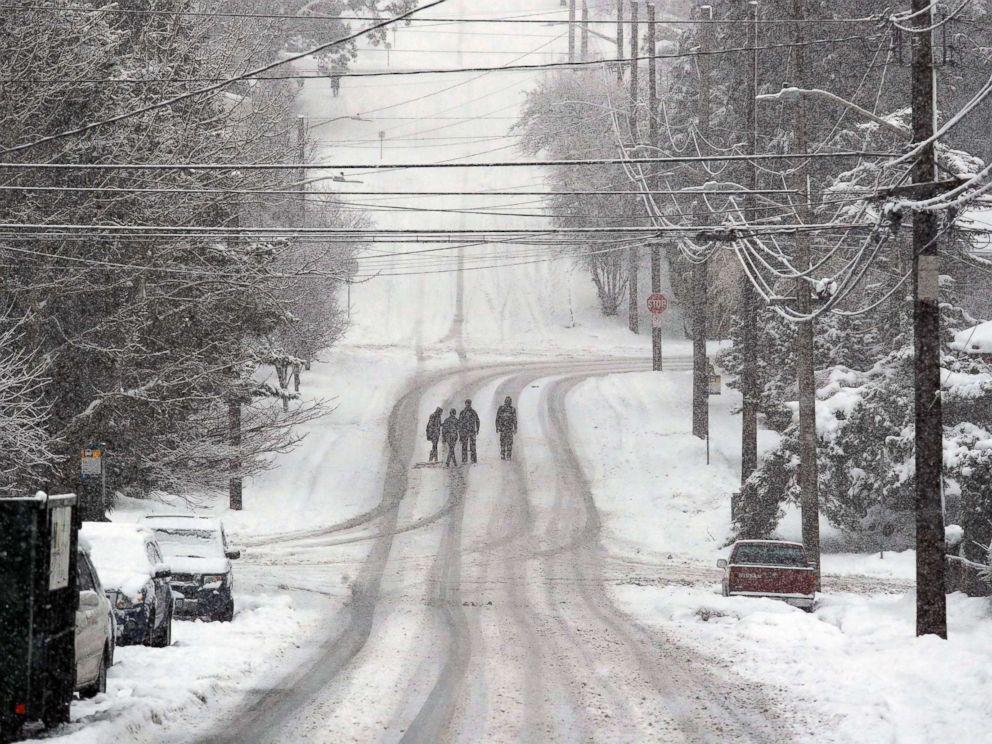 PHOTO: Pedestrians cross a deserted street as heavy snow falls, Feb. 11, 2019, in Seattle.