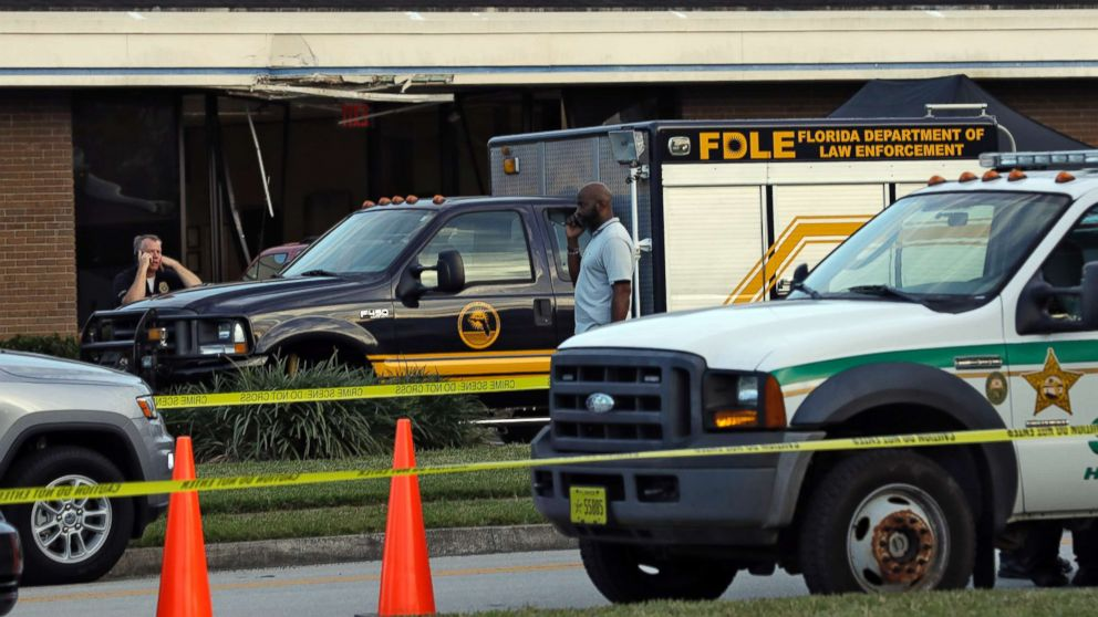 Law Enforcement Officers Stand Near A Florida Department Of Vehicle That Is Parked In