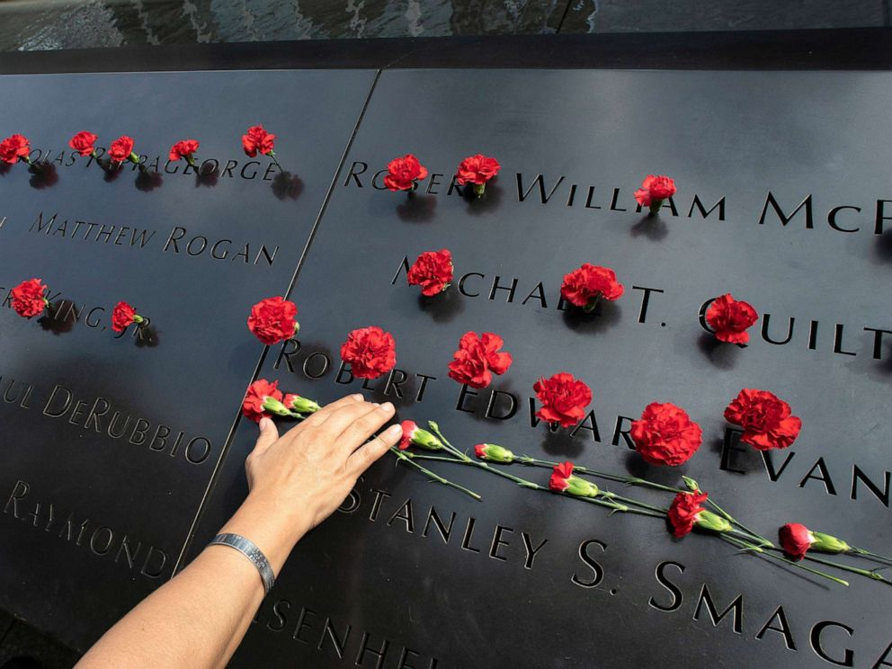 PHOTO: Norma Molina, of San Antonio, Texas, leaves flowers by the names of firefighters from Engine 33 at the September 11 Memorial, Sept. 9, 2019, in New York.