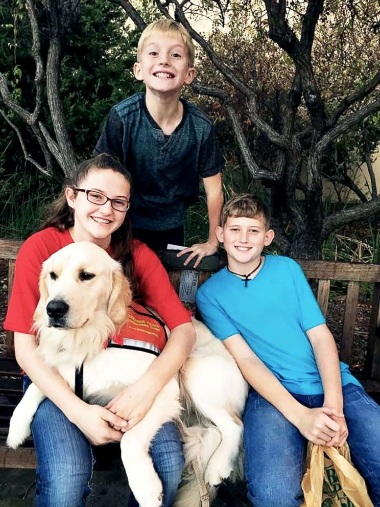 PHOTO: Hannah Westmoreland (left) is pictured with her siblings and her service dog Journey.