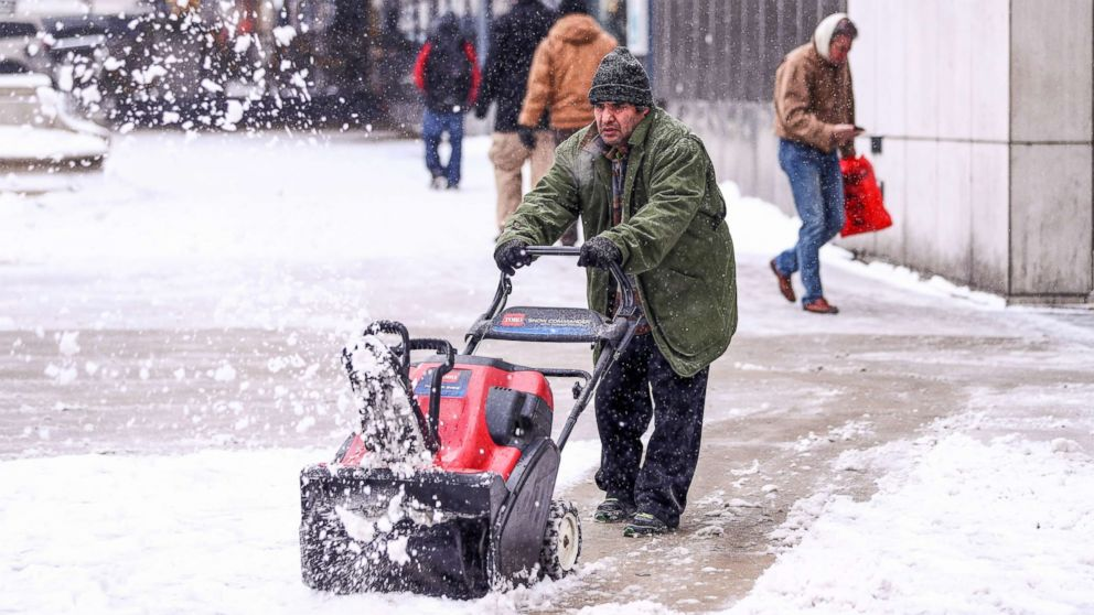 A man cleans a sidewalk with a snowplow during snowfall in Chicago, Dec. 24, 2017.