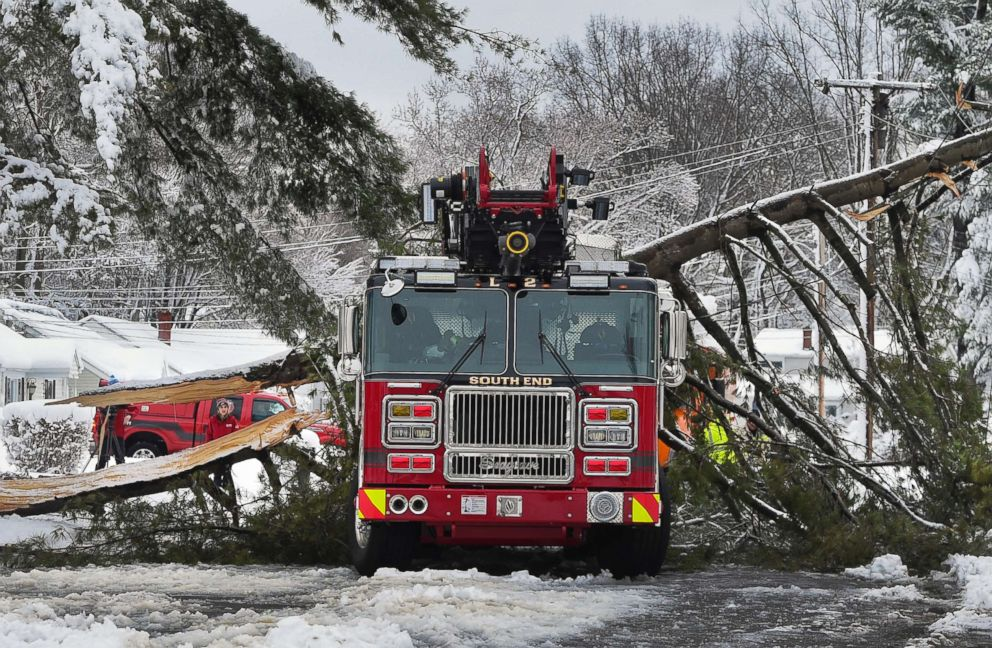 A tree branch fallen from the weight of heavy snow lies on top of a fire truck in East Hartford, Conn., March 8, 2018. The branch that fell took down live power lines and landed onto the truck as it was parked responding to a fire. No one was injured.