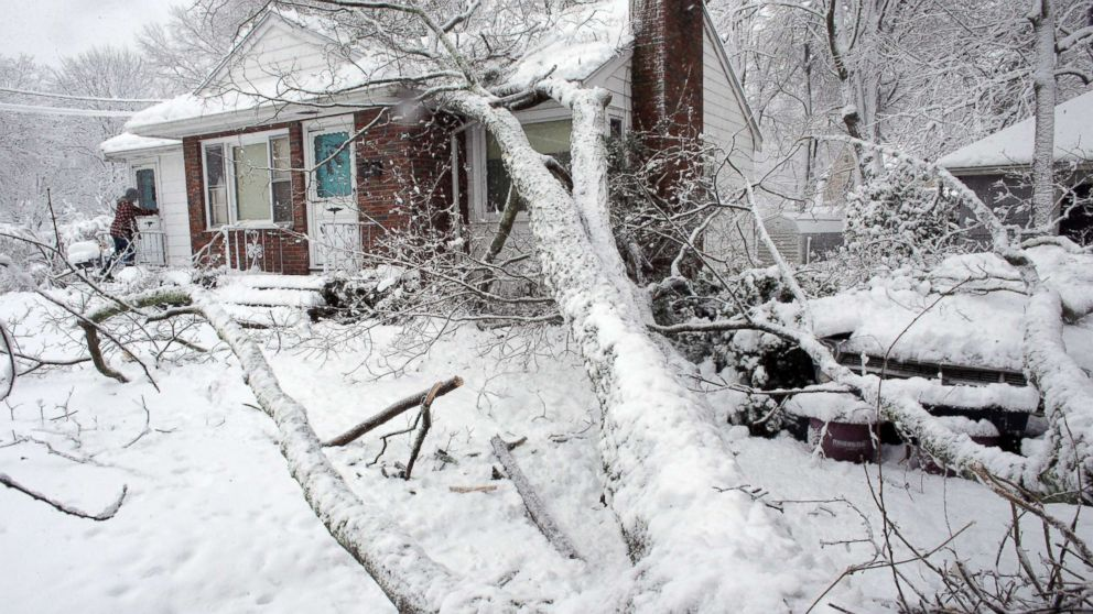 Brian Farrell, of Walpole, Mass., enters his home, March 8, 2018, after a tree fell on the house and a car, right, in Walpole, Mass.