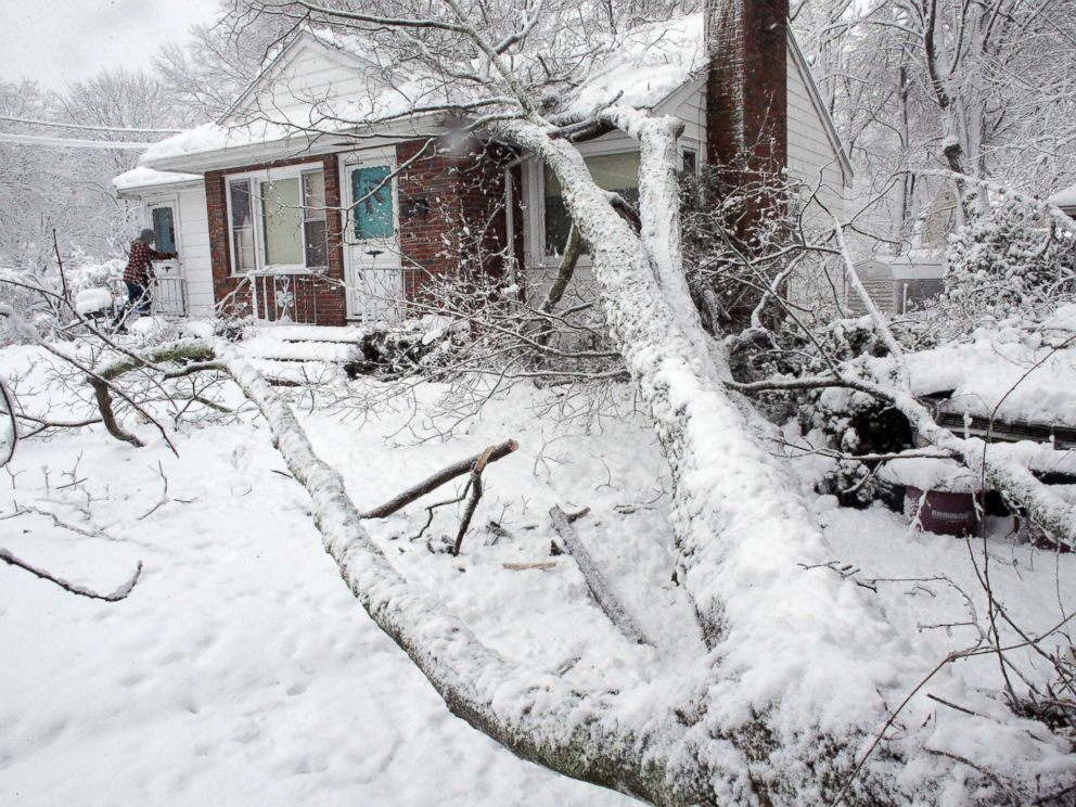 PHOTO: Brian Farrell, of Walpole, Mass., enters his home, March 8, 2018, after a tree fell on the house and a car, right, in Walpole, Mass.