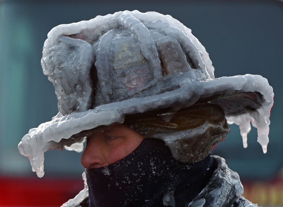 Firefighter Bobby Lehman, with his helmet and bunker gear caked in ice, tries to thaw out after battling a stubborn, wind-driven fire at 238 Wilson Road, Jan. 1, 2018, Nahant, Mass.