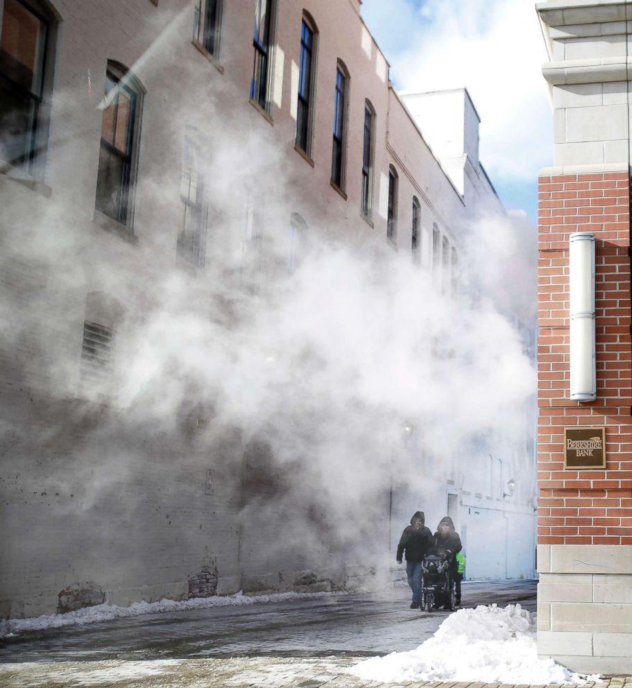 PHOTO: Pedestrians walk through steam from the Berkshire Bank building on North Street during a frigid winter day, Dec. 27, 2017, in Pittsfield, Mass.
