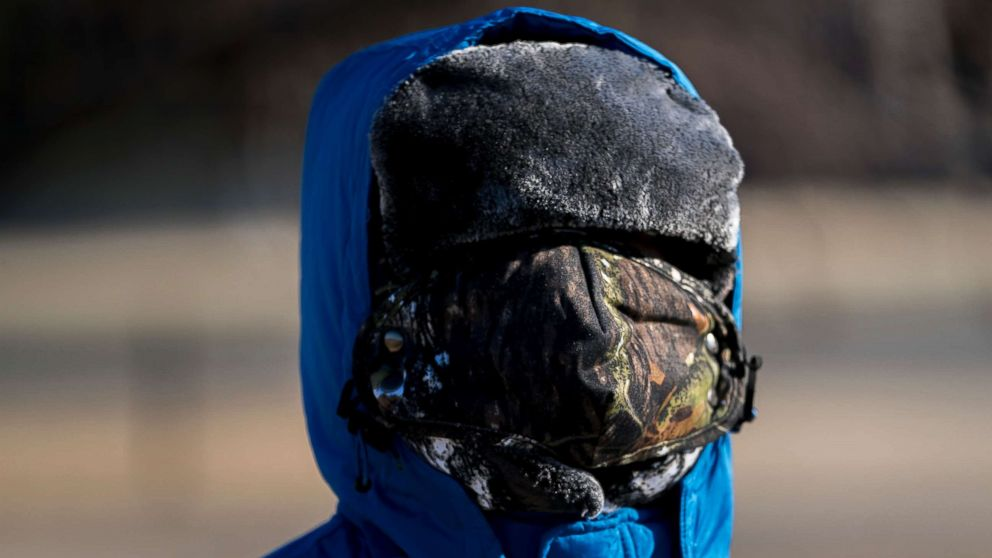 A boy has his face bundled against temperatures in the teens on the National Mall, Dec. 28, 2017, in Washington.