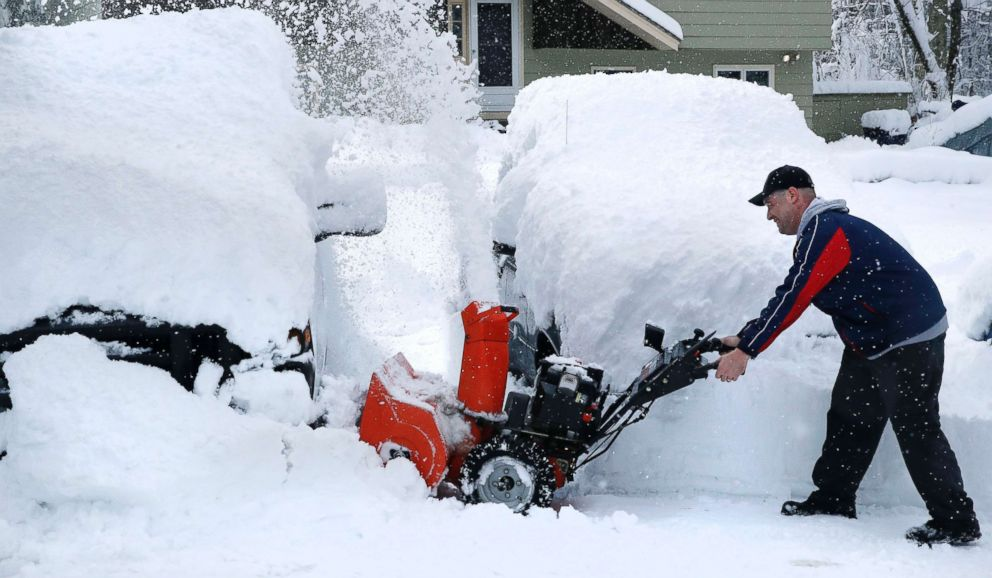 John Visco clears snow from around the cars in his driveway in Derry, N.H., March 8, 2018.