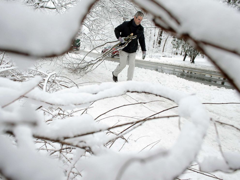 PHOTO: Kevin Crowley, of Weyland, Mass., works to remove damaged tree branches from a driveway, March 8, 2018, in Sherborn, Mass.