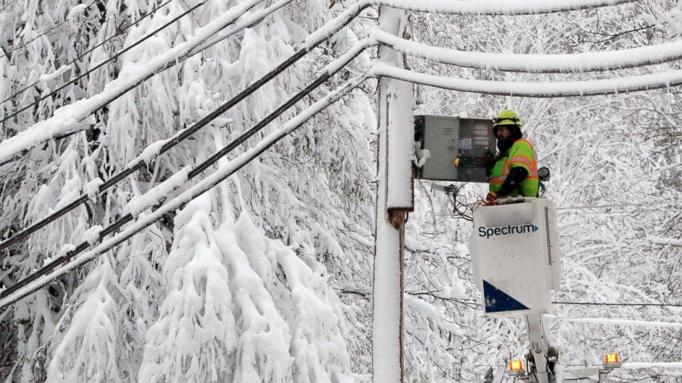 A lineman works to restore power amid limbs sagging with heavy wet snow after a snowstorm, March 8, 2018, in Northborough, Mass.