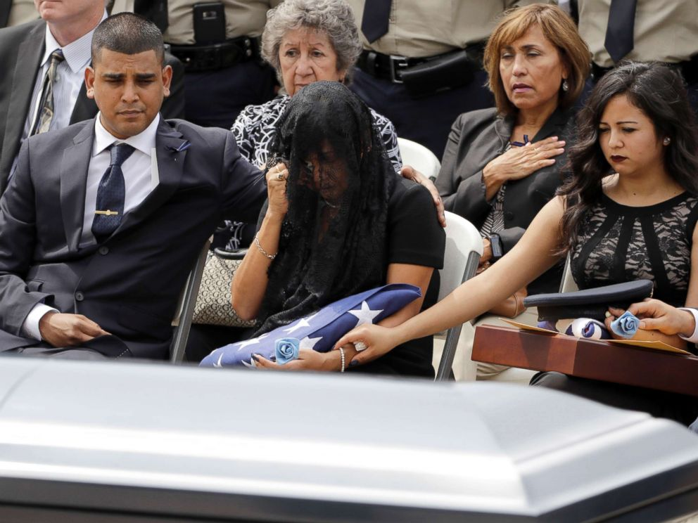 PHOTO: Cheryl Perez, center, is comforted by her son, Maverick, left, and daughter, Sabrina, during a funeral service for her husband, Houston Police Sgt. Steve Perez, Sept. 13, 2017, in Houston.