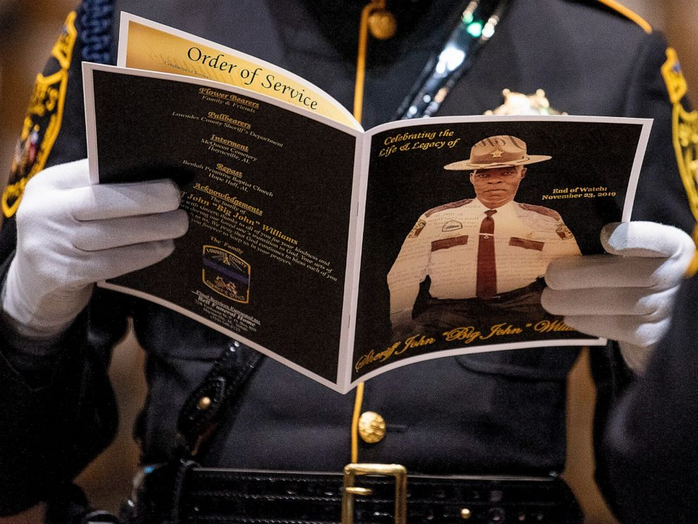 PHOTO: An attendee reads a program during the funeral of Lowndes County Sheriff Big John Williams at Garrett Coliseum in Montgomery, Ala., Dec. 2, 2019.