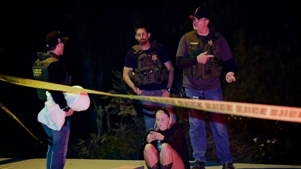Sheriff's deputies speak to a potential witness as they stand near the scene where a gunman opened fire, Nov. 8, 2018, in Thousand Oaks, Calif.