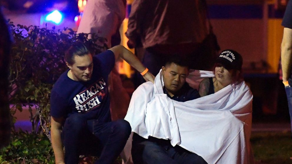 "People comfort each other as they sit near the scene, Nov. 8, 2018, in Thousand Oaks, Calif. where a gunman opened fire Wednesday inside a country dance bar crowded with hundreds of people on ""college night."""