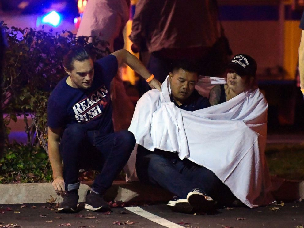 PHOTO: People comfort each other as they sit near the scene, Nov. 8, 2018, in Thousand Oaks, Calif. where a gunman opened fire Wednesday inside a country dance bar crowded with hundreds of people on college night.