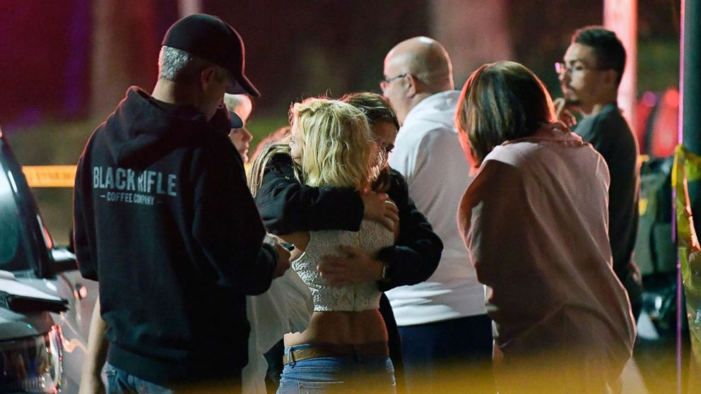 "People comfort each other as they stand near the scene, Nov. 8, 2018, in Thousand Oaks, Calif., where a gunman opened fire Wednesday inside a country dance bar crowded with hundreds of people on ""college night."""