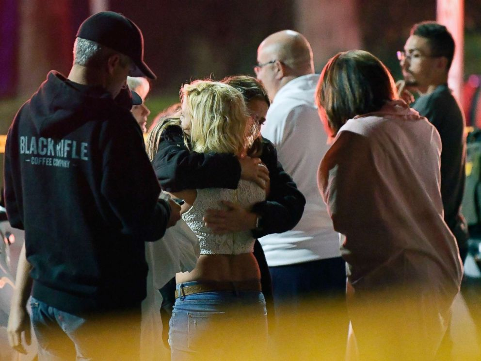 PHOTO: People comfort each other as they stand near the scene, Nov. 8, 2018, in Thousand Oaks, Calif., where a gunman opened fire Wednesday inside a country dance bar crowded with hundreds of people on college night.