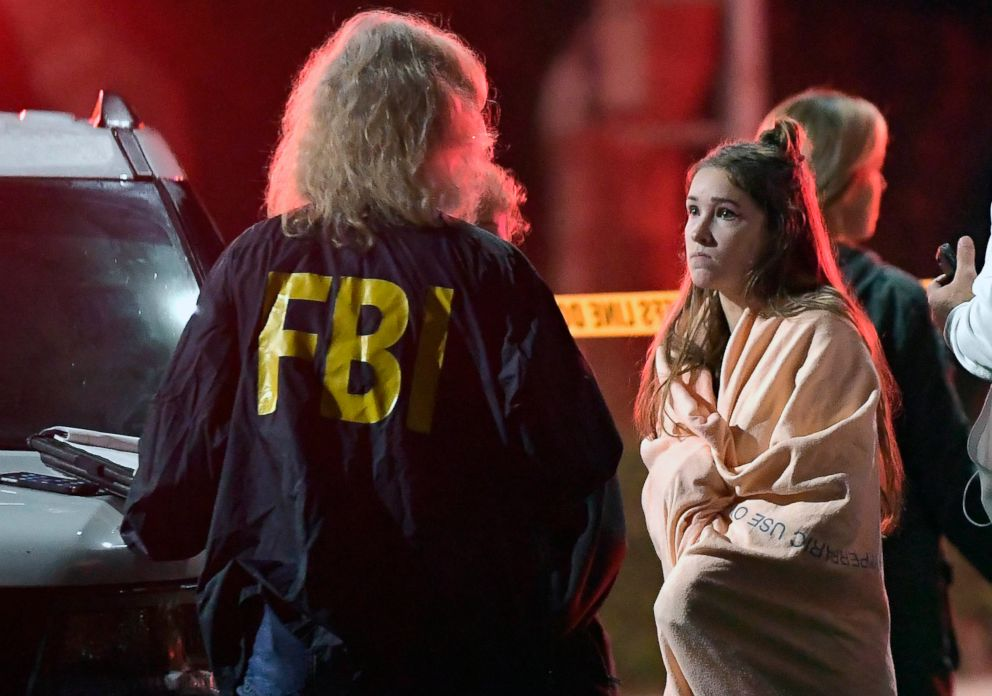 PHOTO: An FBI agent talks to a potential witness as they stand near the scene, Nov. 8, 2018, in Thousand Oaks, Calif. where a gunman opened fire Wednesday inside a country dance bar crowded with hundreds of people on college night.