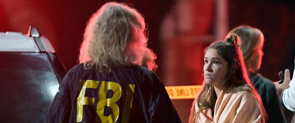 "PHOTO: An FBI agent talks to a potential witness as they stand near the scene, Nov. 8, 2018, in Thousand Oaks, Calif. where a gunman opened fire Wednesday inside a country dance bar crowded with hundreds of people on ""college night."""