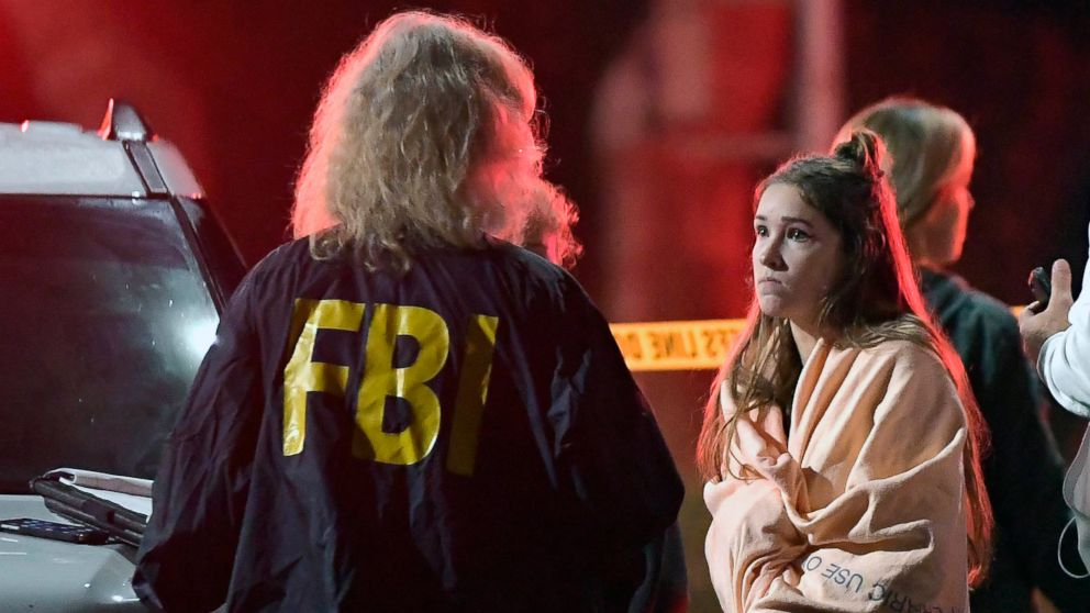 """An FBI agent talks to a potential witness as they stand near the scene, Nov. 8, 2018, in Thousand Oaks, Calif. where a gunman opened fire Wednesday inside a country dance bar crowded with hundreds of people on """"college night."""""""