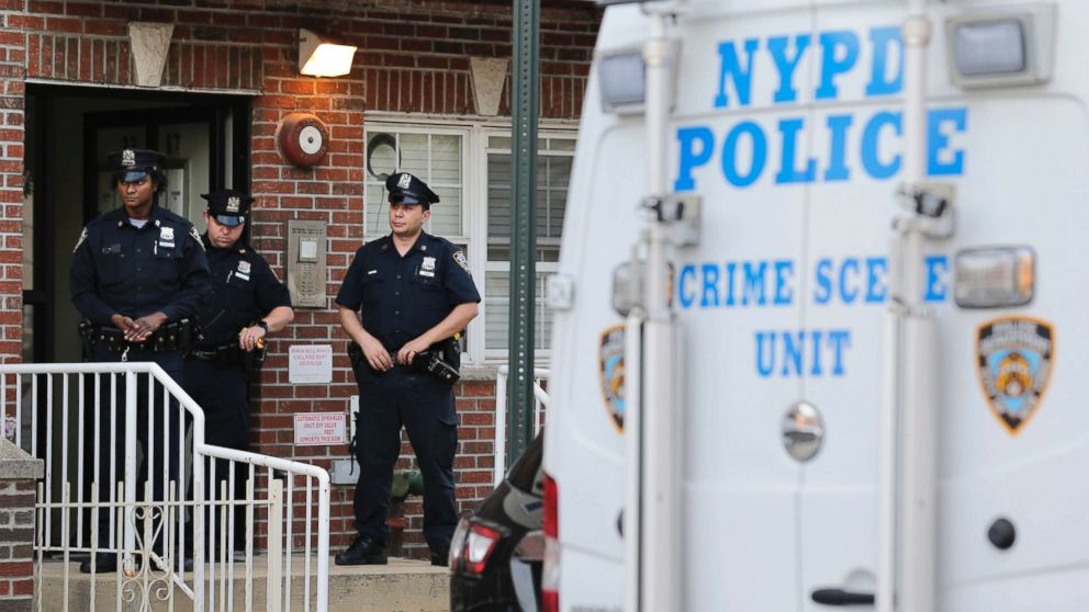 Police officers stand in front of a building where there was a shooting with multiple fatalities in the Queens borough of New York, July 31, 2018.
