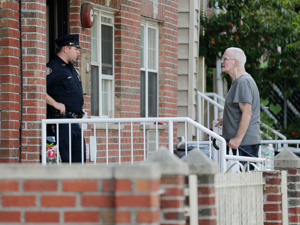 PHOTO: A police officer, left, talks with James Shields, Sr. in front a building where there was a shooting with multiple fatalities, including his son, in the Queens borough of New York, July 31, 2018.