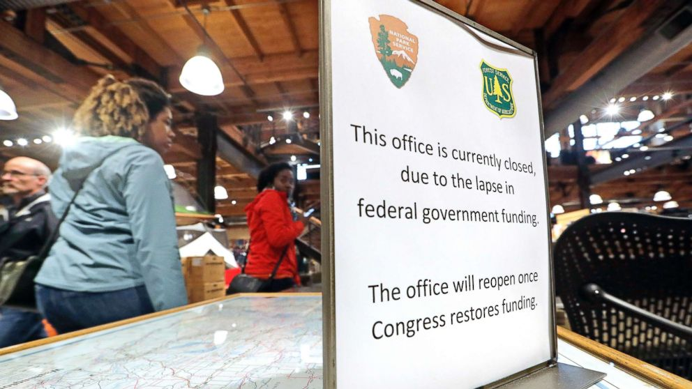 REI Co-op customers walk past an unstaffed ranger station kiosk, closed as part of the federal government shutdown, inside the flagship store in Seattle, Dec. 26, 2018.