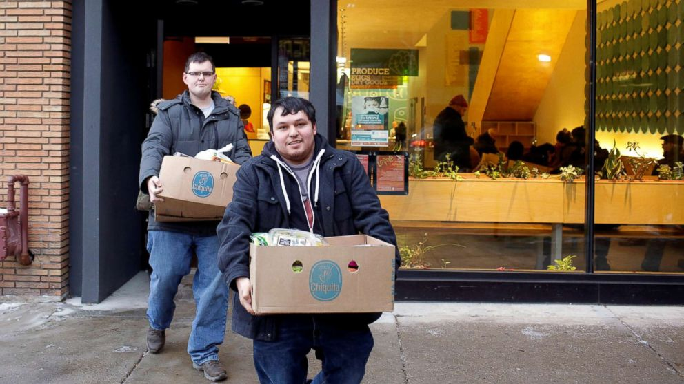 TSA worker John Salinas, right, and his fiancee Ryan Farmer leave the Lakeview Pantry after receiving food in Chicago, Jan. 14, 2019.
