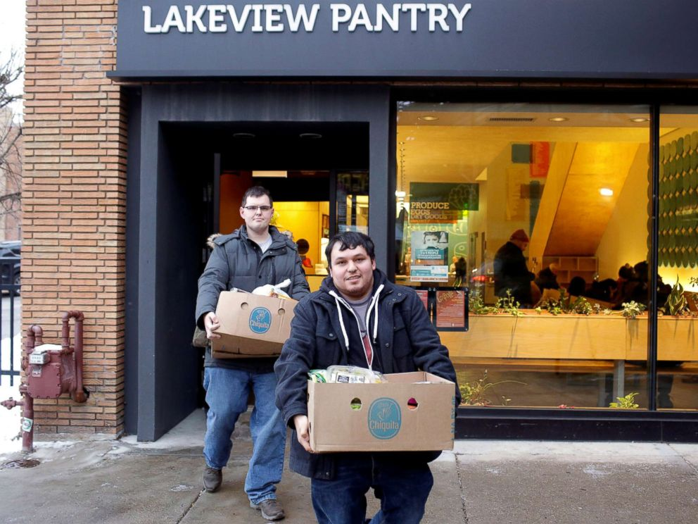 PHOTO: TSA worker John Salinas, right, and his fiancee Ryan Farmer leave the Lakeview Pantry after receiving food in Chicago, Jan. 14, 2019.