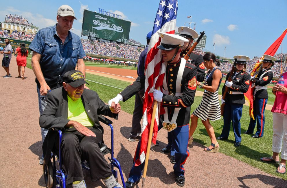 PHOTO: World War II veteran Sidney Walton, left, is greeted by a member of the color guard before a baseball game between the Chicago Cubs and Detroit Tigers, July 4, 2018, in Chicago.