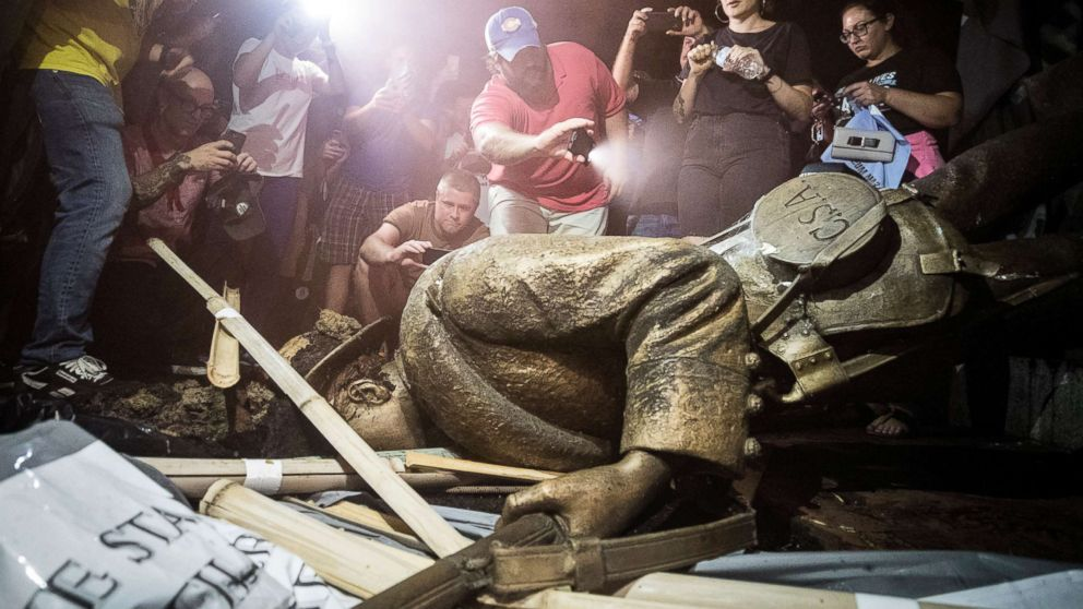 Demonstrators and spectators gather around a toppled Confederate statue known as Silent Sam, Aug. 20, 2018 at UNC-Chapel Hill, N.C.