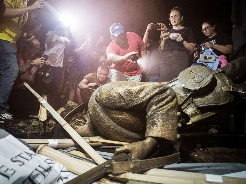 PHOTO: Demonstrators and spectators gather around a toppled Confederate statue known as Silent Sam, Aug. 20, 2018 at UNC-Chapel Hill, N.C