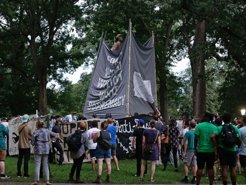 Banners are used to cover the statue known as Silent Sam as people gather during a rally to remove the confederate statue from campus at the University of North Carolina in Chapel Hill, N.C., Monday, Aug. 20, 2018.